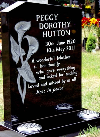 Scott Taylor top UK stone sculptor & stonemason carved this black granite memorial which was complemented with shot-blasted hand cut stencil letters. This stands as a good example of retaining the spontaneity and individual nature of handmade work while working within a competitive budget. The carving does not use any paint and will last indefinitely due to the remarkably hard nature of the material.